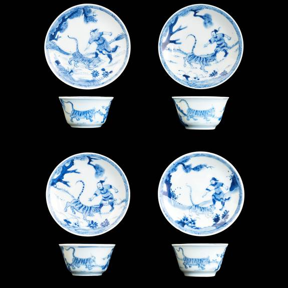 Four Chinese porcelain blue and white teabowls and saucers with Wusong slaying a tiger