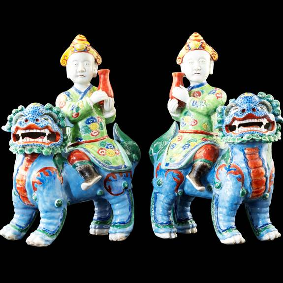 GG: Pair of Chinese porcelain famille rose figures of riders on Buddhist lions